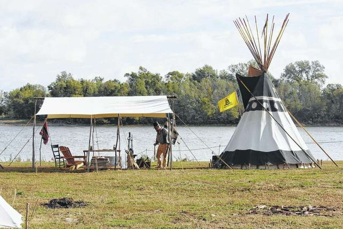 A man sets up camp on the banks of the Illinois River during Kampsville Old Settler Days. The event, which recalls the early days of Calhoun County, includes campers who spend the weekend living in teepees or canvas tents.
