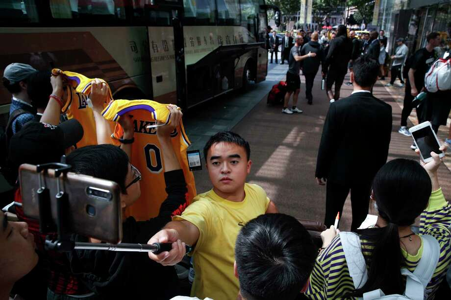 Fans take smartphone selfies and show off their LA Lakers jerseys as NBA players step out from a bus outside the Ritz-Carlton hotel in Shanghai, China, Thursday, Oct. 10, 2019. NBA Commissioner Adam Silver told the Brooklyn Nets and Los Angeles Lakers on Wednesday that the league is still expecting them to play as scheduled this week, even while the rift between the league and Chinese officials continued in ways that clearly suggested the two planned games in Shanghai and Shenzhen were anything but guaranteed. Photo: Andy Wong, AP / Copyright 2018 The Associated Press. All rights reserved