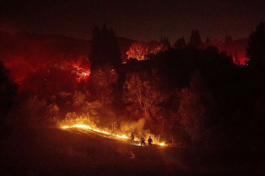 Firefighters work to contain a wildfire burning off Merrill Dr. in Moraga, Calif., on Thursday, Oct. 10, 2019. Police have ordered evacuations as the fast-moving wildfire spread in the hills of the San Francisco Bay Area community. The area is without power after Pacific Gas & Electric preemptively cut service hoping to prevent wildfires during dry, windy conditions throughout Northern California. (AP Photo/Noah Berger) Photo: Noah Berger / Associated Press