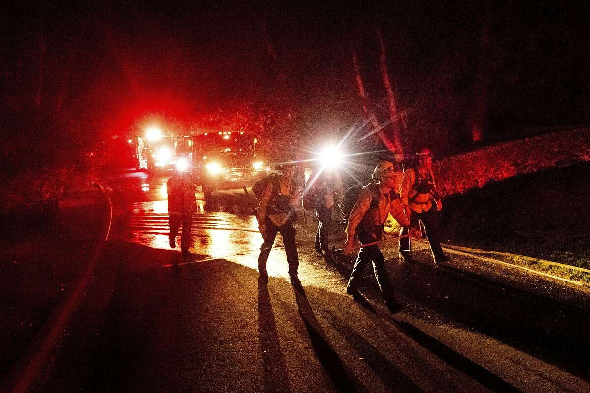 Firefighters work to contain a wildfire burning off Merrill Dr. in Moraga, Calif., on Thursday, Oct. 10, 2019. The area is without power after Pacific Gas and Electric preemptively cut service hoping to prevent wildfires during dry, windy conditions throughout Northern California. (AP Photo/Noah Berger)