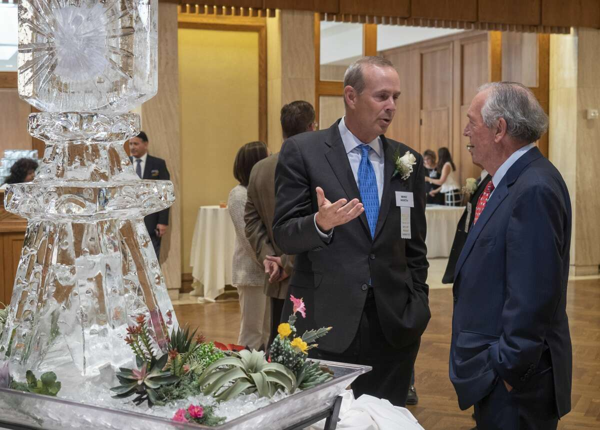 Chevron CEO Mike Wirth, left, talks with Don Evans Wednesday before the Midland Wildcat Committee honors Chevron.