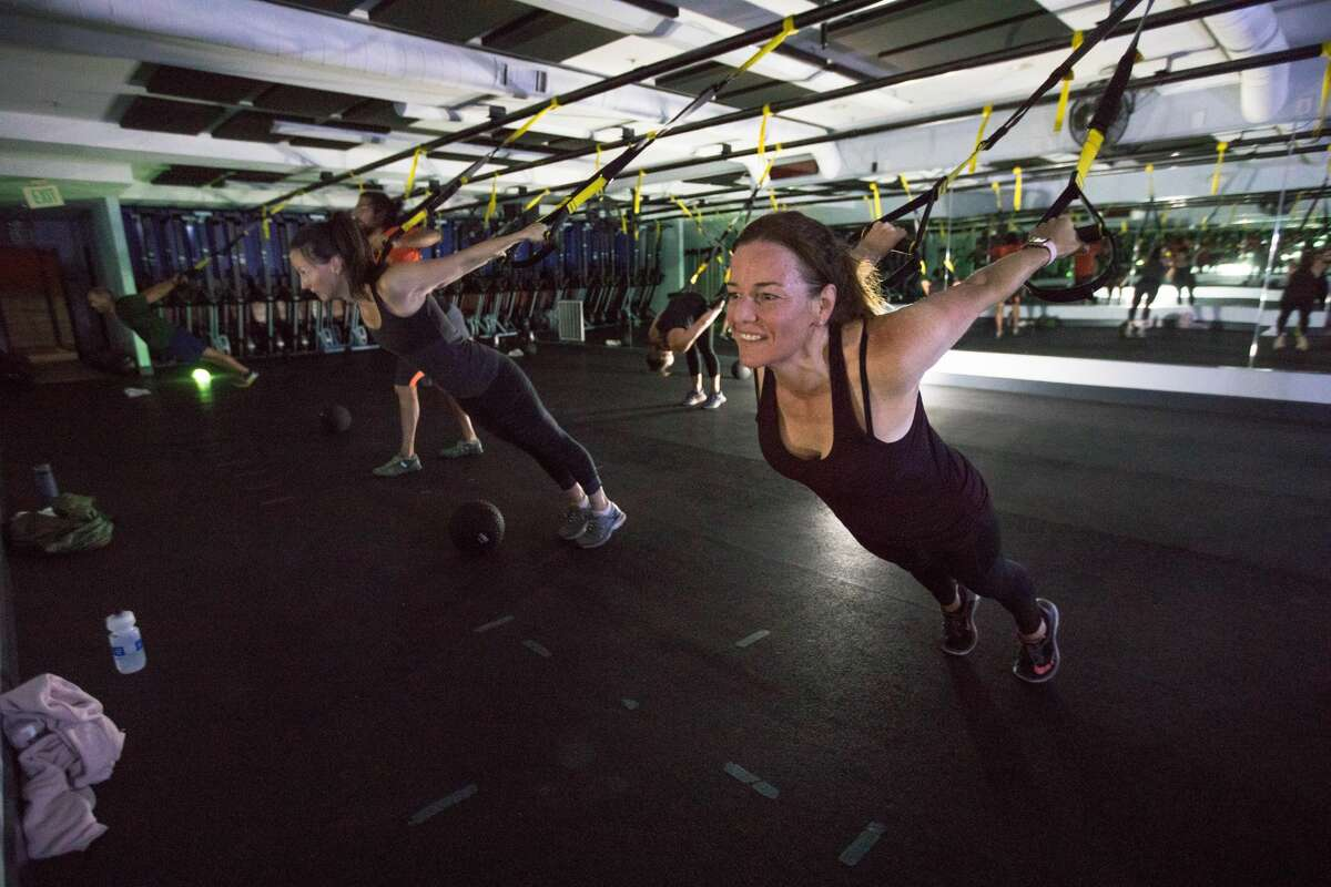 Despite a power outage (right to left) Sylvia Stephenson and Lindsay Grassock take part in a morning boot camp class using lanterns at Cru Fit fitness studio In the Montclair neighborhood of Oakland, Calif. on Oct. 10, 2019. PG&E cut power to customers in Northern California and the East Bay to prevent wildfires during dry, windy weather throughout the region.
