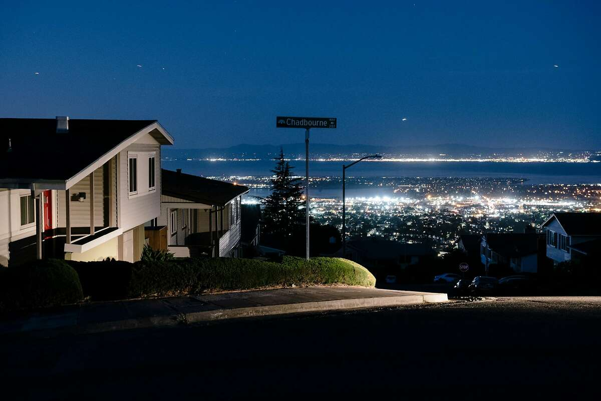 Oakland city lights are seen in the distance behind darkened homes off of Skyline Boulevard in Oakland, California, on Friday, Oct. 10, 2019. PG&E planned power outages affected parts of Oakland and Alameda County as the utility fights to stave off wildfires that can be caused by high winds hitting their power lines.