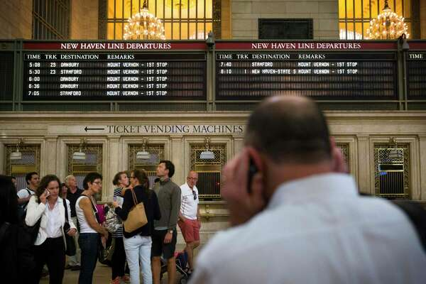 A depopulated New Haven transit line departures board looms over commuters as they use their cellphones at Grand Central Terminal.