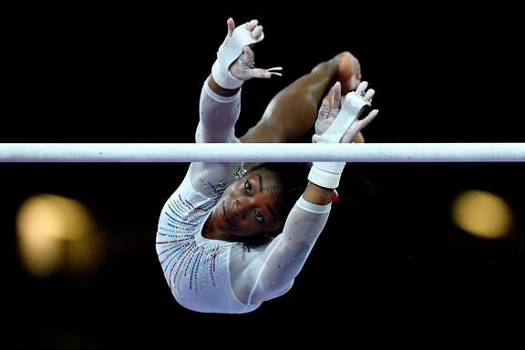 USA's Simone Biles performs on the uneven bars during the women's all-around final at the FIG Artistic Gymnastics World Championships at the Hanns-Martin-Schleyer-Halle in Stuttgart, southern Germany, on October 10, 2019. (Photo by Thomas KIENZLE / AFP)