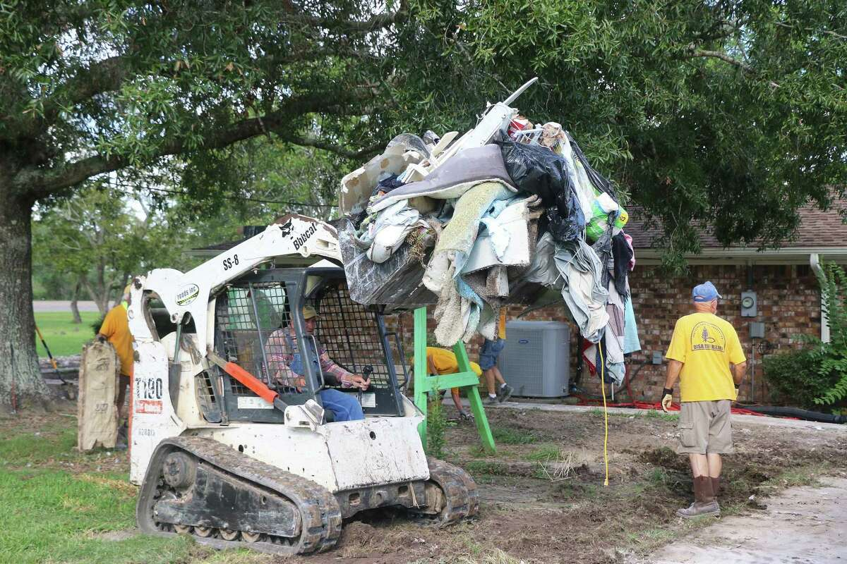 Ron Culberson steps out of the way of the bobcat driven by Dewey Lewis who loads up mounds of debris and soaked clothes from Imelda's wrath.