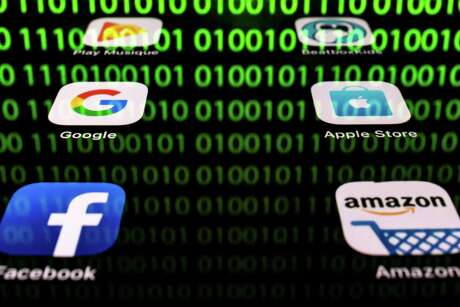"""(FILES) In this file photo taken on April 20, 2018 shows an illustration picture in Paris shows apps for Google, Amazon, Facebook, Apple (GAFA) and the reflexion of a binary code displayed on a tablet screen. - The OECD published on October 9, 2019, its suggestions for a """"unified approach"""" on fairly taxing digital giants to break a deadlock in a dispute that has raised tensions between the United States and some EU allies. (Photo by Lionel BONAVENTURE / AFP) (Photo by LIONEL BONAVENTURE/AFP via Getty Images)"""