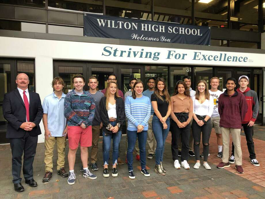 Wilton High School Principal Robert O'Donnell joins 15 of the school's 16 National Merit Commended Students. From left in front are Jackson Lent, Wictoria Matuk, Emma Babashak, Isabel Gouveia, Claudia Nanez, Katherine Buse and Dineth Karunamuni. In back are Justin Lipper, Zachary Muraskin, Devan Flores, Avi Sardana, Navod Jayawardhane, Nishant Wangneo, Alexander Schestag and Noah Sackowitz. Missing from photo is Larry Huang. Photo: Contributed Photo / Wilton High School / Wilton Bulletin Contributed