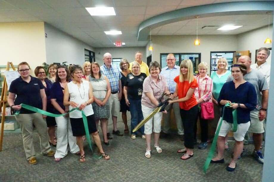 RIBBON CUTTING: Christine Cox, president of the Reed City Area Public Library board, and Heather Symon Bassett, Library Director at the Reed City Public Library, cut the ribbon to officially open the new library location on South Chestnut Street in Reed City.