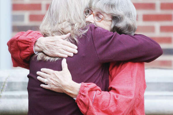 Donna Clendenny, right, a speaker at the 15th annual Domestic Violence Memorial Service Wednesday night, is hugged by Susan Nonn, wife of Madison County Coroner Steve Nonn, after her presentation at Alton Memorial Hospital.
