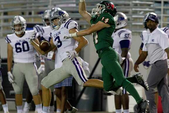 Klein Cain wide receiver Cole Monago (3) makes a one-handed catch as The Woodlands defensive back Carter Doucet (14) for a 83-yard touchdown during the first quarter of a District 15-6A high school football game at Woodforest Bank Stadium, Friday, Oct. 4, 2019, in Shenandoah.
