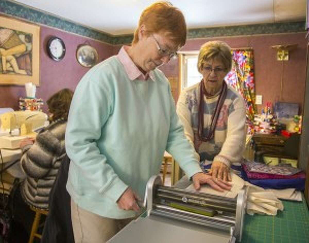 LEARNING: Ruth Cook teaches Denise Justus how to use the Accuquilt Go machine, which cuts precise and consistent shapes into fabric.