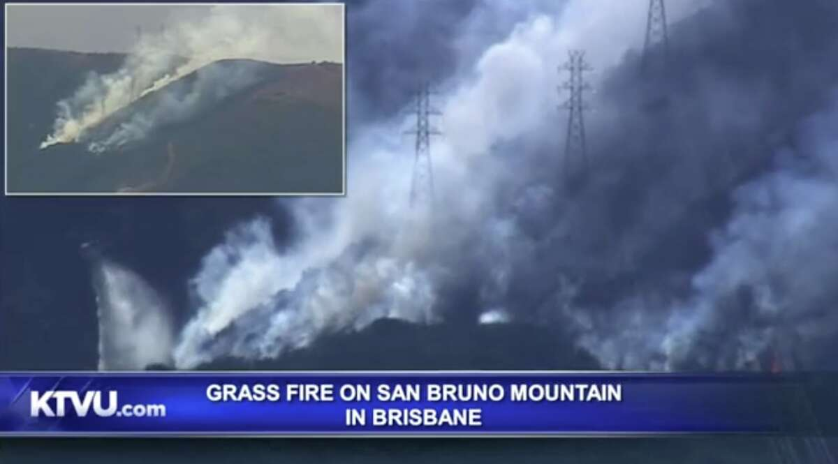 A helicopter drops water on the fire on San Bruno Mountain near Brisbane on Oct. 10, 2019.