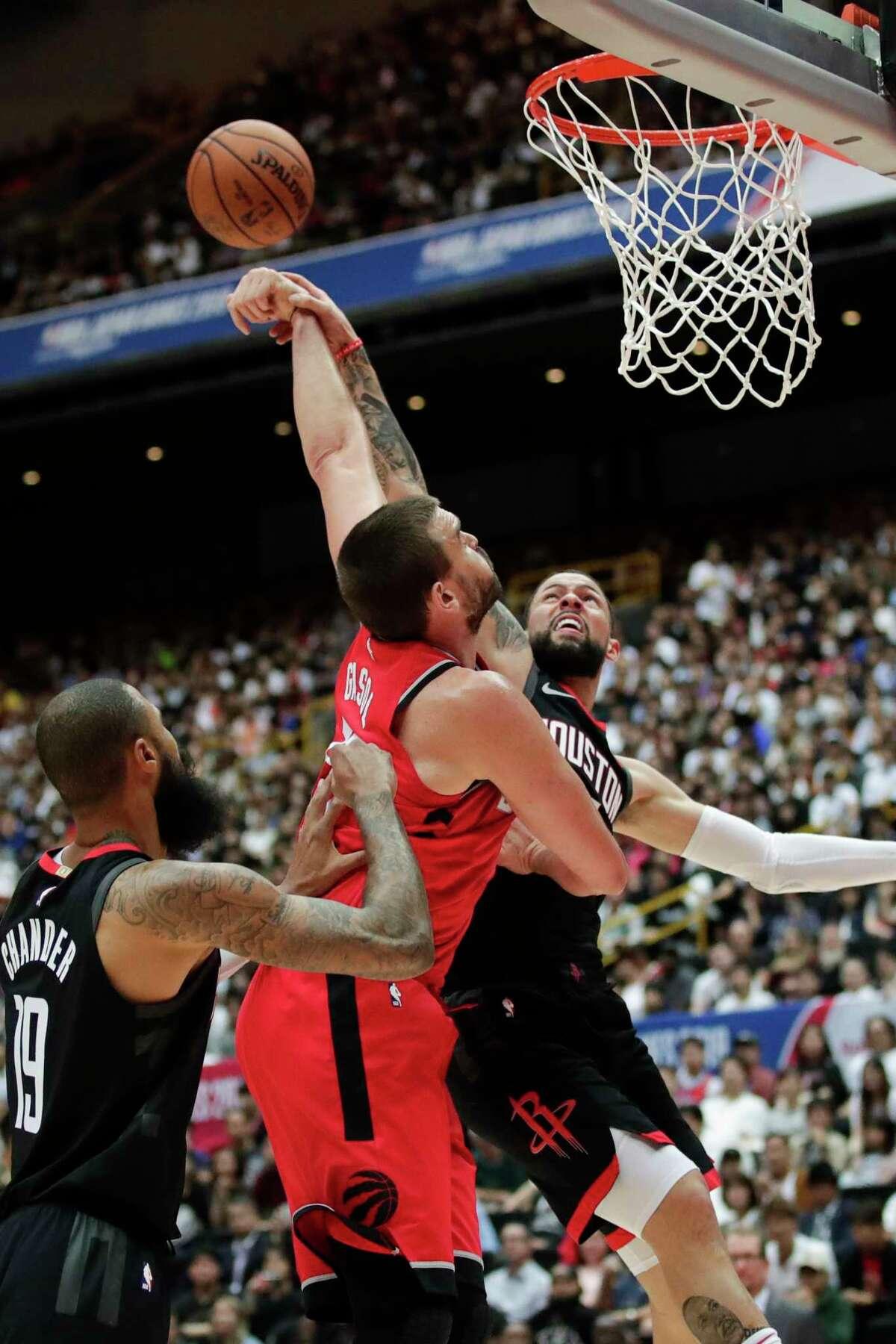 Toronto Raptors' Marc Gasol, center left, is defended by Houston Rockets' Austin Rivers during the first half of an NBA preseason basketball game Thursday, Oct. 10, 2019, in Saitama, near Tokyo. (AP Photo/Jae C. Hong)