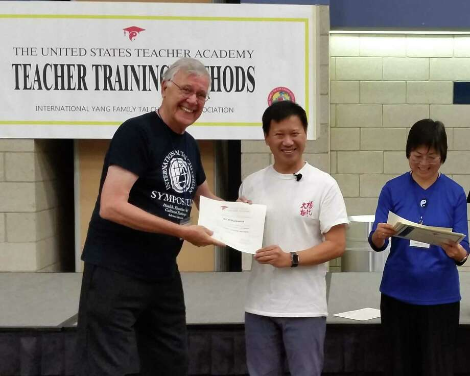 Ridgefield resident Bil Mikulewicz, left, receives a certification renewal from Grand Master Yang Jun as a teacher of traditional Yang Family Tai Chi Chun after a four-day teacher training seminar. Mari Lewis, director of the United States Teacher Academy, looks on at the WCSU campus in Danbury. Mr. Mikulewicz teaches at the Cannon Grange in Wilton. Photo: Contributed Photo