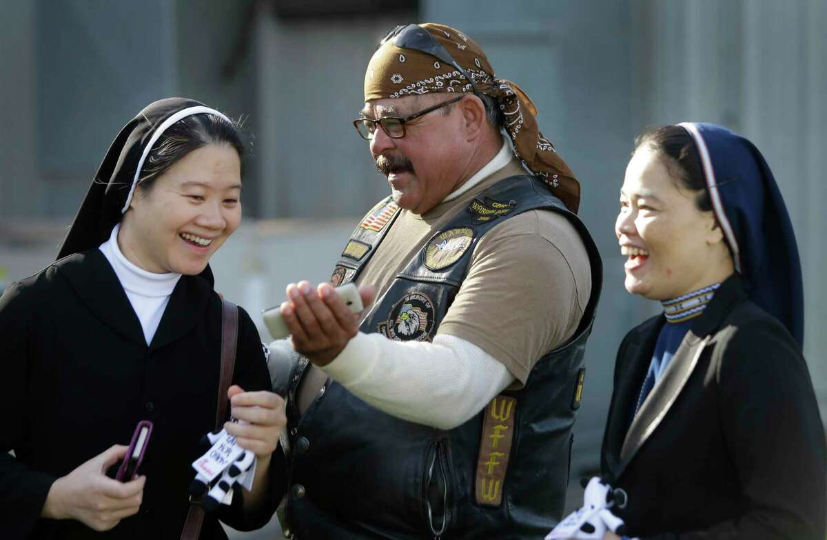 Sister Mary Oanh Ta, left, and Sister Robert Maria Trang, right, laugh as they look at cell phone photos of themselves posing on motorcycles taken by Henry Beretta, center, a member of Warriors Bikers for Christ Motorcycle Ministry, during the 11th Annual Nun Run at St. Austin Center, 2002 S. Wayside Drive, Saturday, Oct. 17, 2015, in Houston. The 40 mile ride to San Leon benefits the CHRISTUS Foundation for HealthCare school-based clinics, which provide healthcare to children on campus in 17 low-income neighborhood schools. ( Melissa Phillip / Houston Chronicle )
