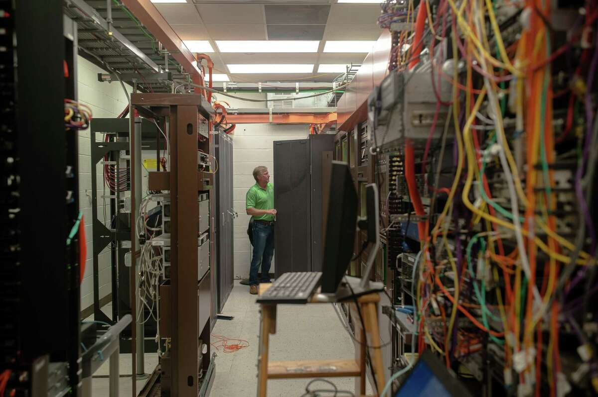 Jerry Whisenhunt checks his Huawei network equipment on Oct. 2 at Pine Telephone Company headquarters in Broken Bow, Okla.