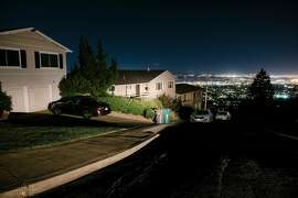 Oakland city lights are seen in the distance behind darkened homes off of Skyline Boulevard in Oakland, California, on Friday, Oct. 10, 2019. The PG&p; planned power outages have affected hundreds of thousands of Californians, and columnist Caille Millner notes that California's ability to produce disaster is outstripping our own imaginations for it.