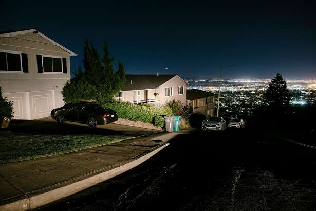Oakland city lights are seen in the distance behind darkened homes off of Skyline Boulevard in Oakland, California, on Friday, Oct. 10, 2019. The PG planned power outages have affected hundreds of thousands of Californians, and columnist Caille Millner notes that California's ability to produce disaster is outstripping our own imaginations for it.