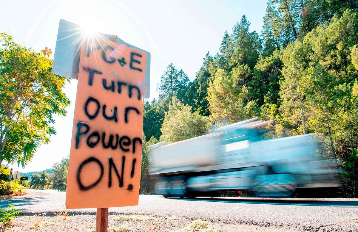 FILE - A sign calling for PG&E to turn the power back on is seen on the side of the road during a statewide blackout in Calistoga on Oct. 10, 2019 - Rolling blackouts set to affect millions of Californians began October 9, as Pacific Gas & Electric started switching off power to an unprecedented number of households in the face of hot, windy weather that raises the risk of wildfires.