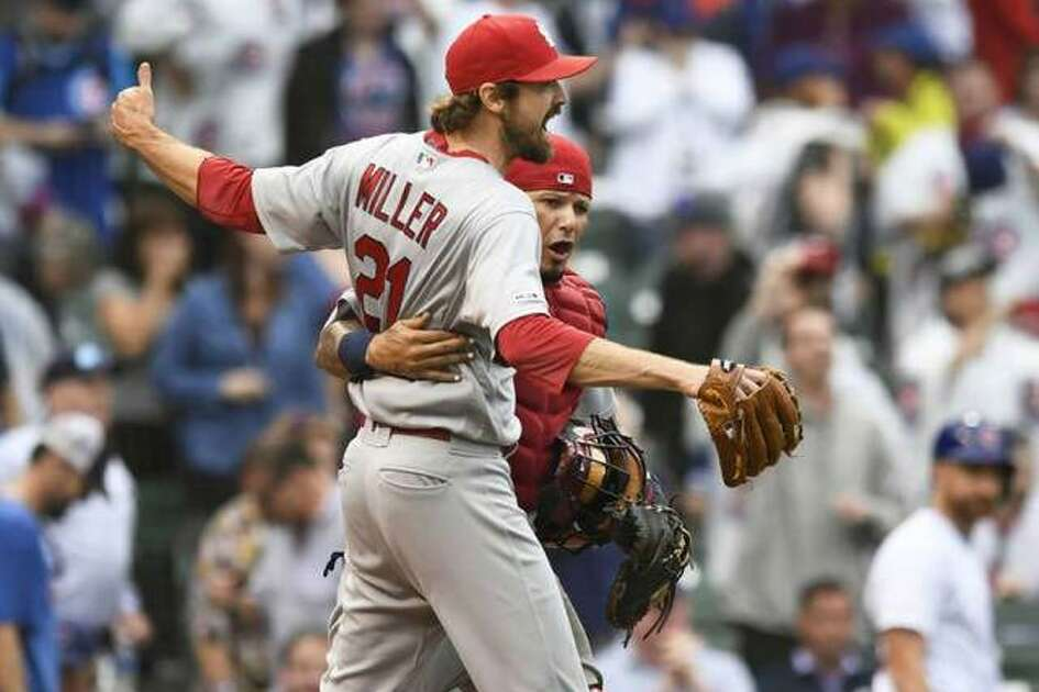 Cardinals pitcher Andrew Miller celebrates with catcher Yadier Molina after defeating the the Chicago Cubs in a game Sunday in Chicago. The win gave the Cards a four-game series sweep and clinched a postseason berth for St. Louis. AP.