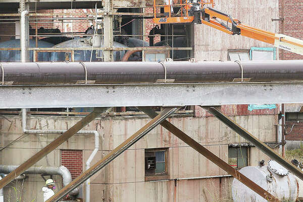 Workers wearing respirators disassemble a part of the former Wood River Power Station in East Alton Thursday. The site is under demolition and remediation.