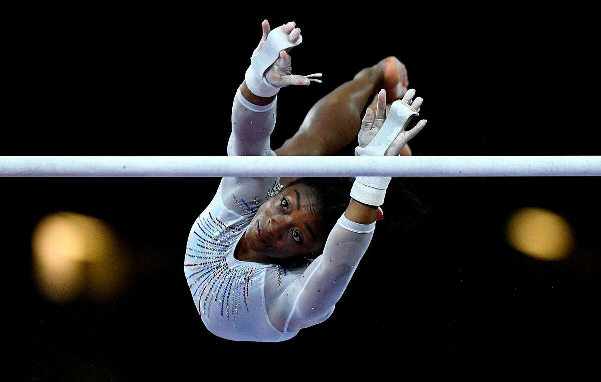 TOPSHOT - USA's Simone Biles performs on the uneven bars during the women's all-around final at the FIG Artistic Gymnastics World Championships at the Hanns-Martin-Schleyer-Halle in Stuttgart, southern Germany, on October 10, 2019. (Photo by Thomas KIENZLE / AFP) (Photo by THOMAS KIENZLE/AFP via Getty Images)