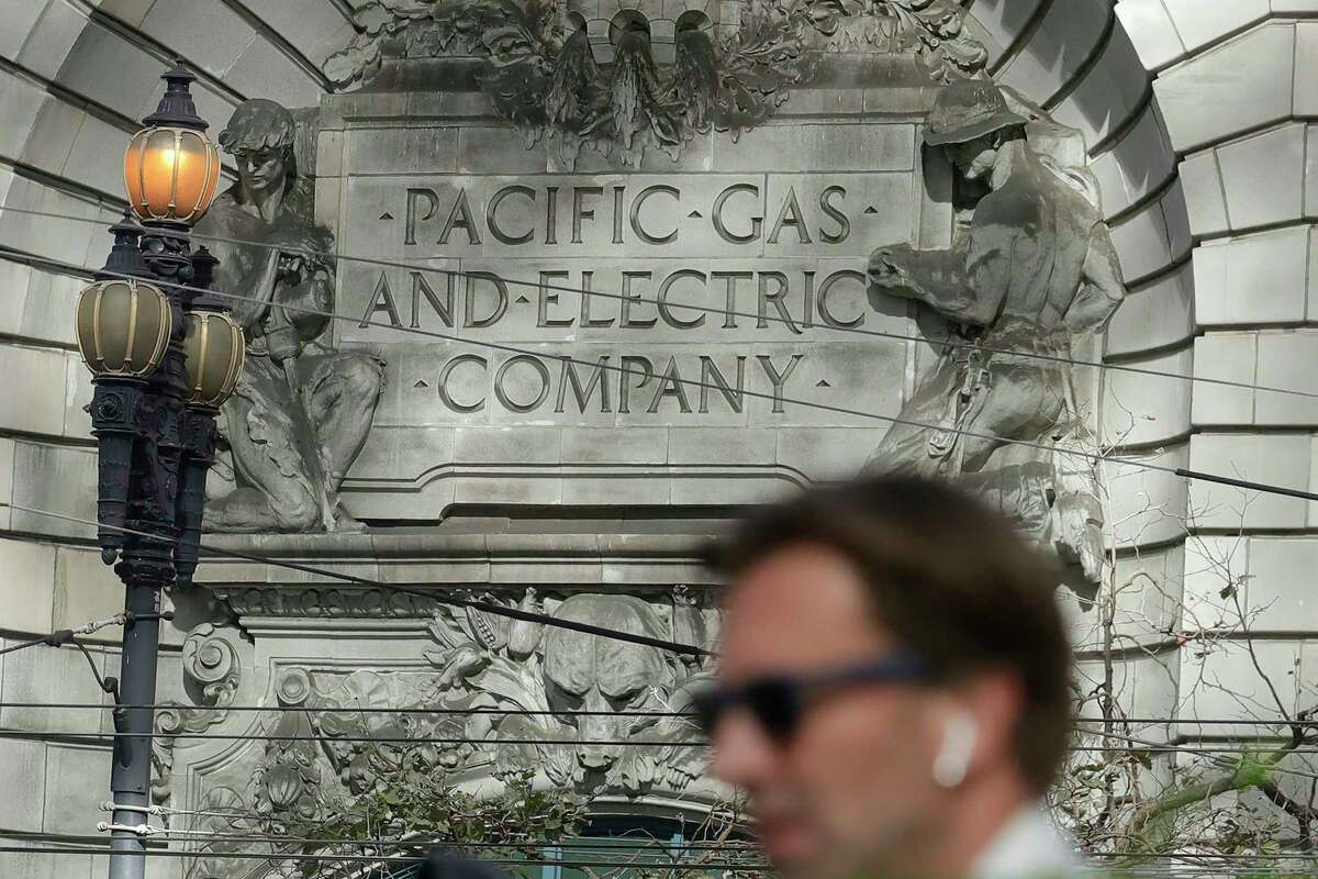 FILE - A man walks across the street under a Pacific Gas & Electric sign outside of a PG&E building in San Francisco, Thursday, Oct. 10, 2019. More than 1.5 million people in Northern California were in the dark Thursday, most for a second day, after the state's biggest utility shut off electricity to many areas to prevent its equipment from sparking wildfires as strong winds sweep through.