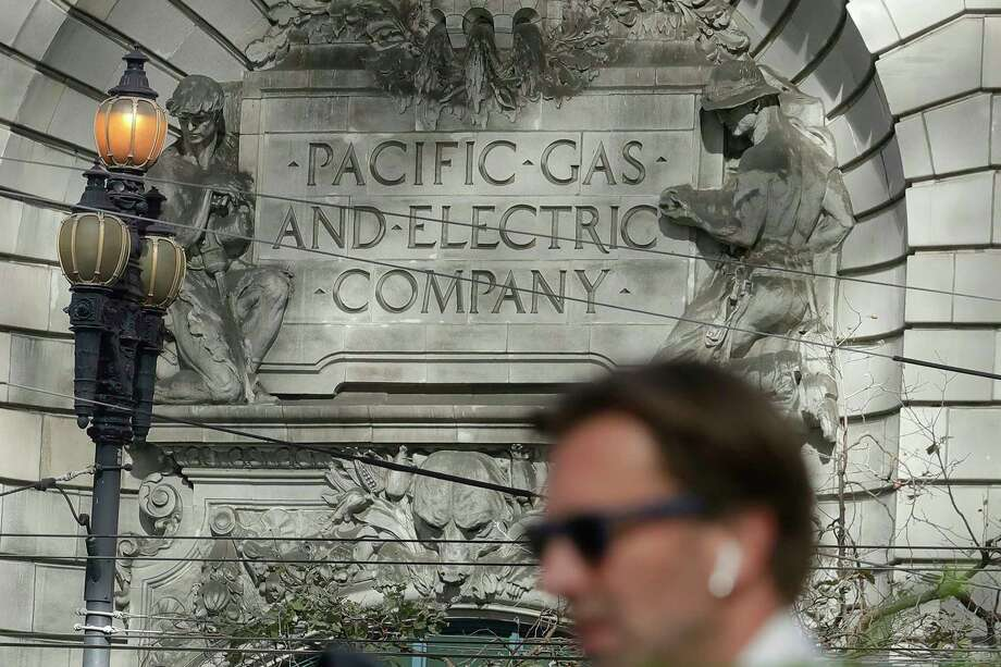 FILE - A man walks across the street under a Pacific Gas & Electric sign outside of a PG&E building in San Francisco, Thursday, Oct. 10, 2019. More than 1.5 million people in Northern California were in the dark Thursday, most for a second day, after the state's biggest utility shut off electricity to many areas to prevent its equipment from sparking wildfires as strong winds sweep through. Photo: Jeff Chiu, AP / Copyright 2019 The Associated Press. All rights reserved