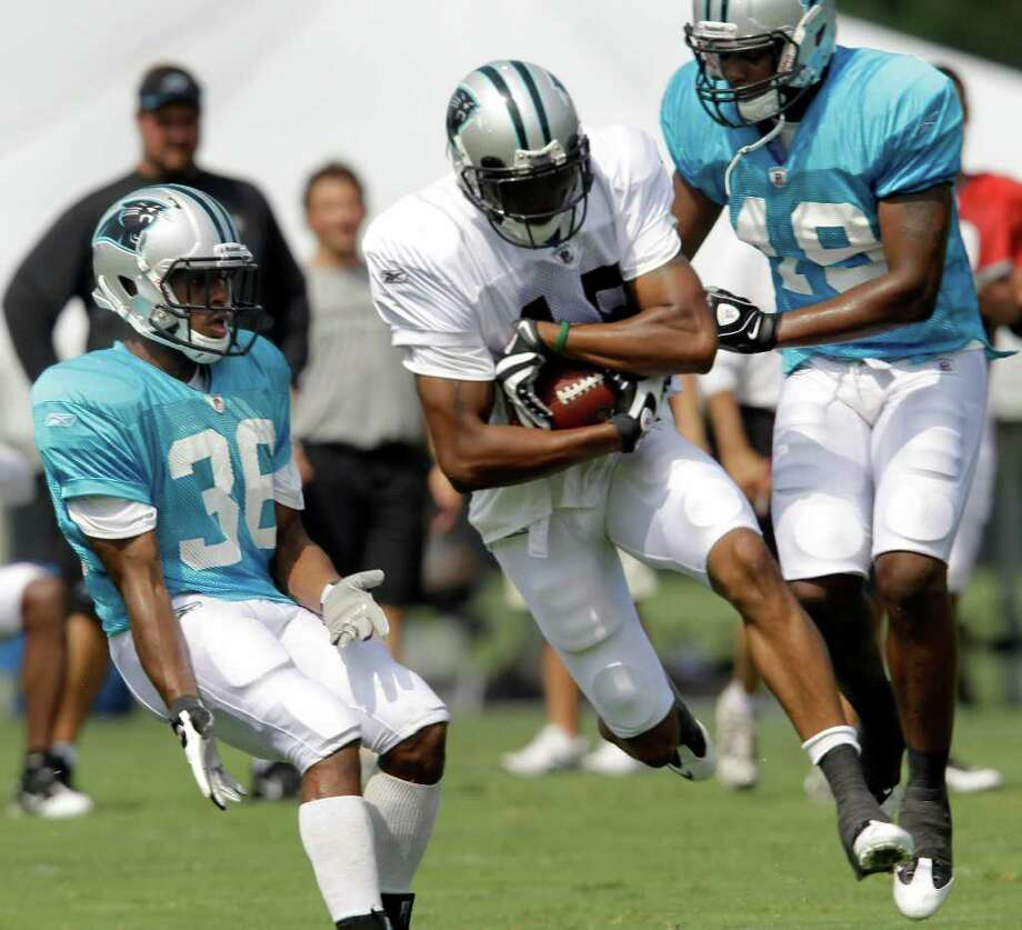 In this July 30, 2010 photo Carolina Panthers Robert McClain (36) and Sean Ware (49) defend as Oliver Young (18) catches a pass during practice at the NFL football team's training camp in Spartanburg, S.C. McClain's impressive Panthers training camp comes as he still thinks about his former Connecticut teammate, Jasper Howard, who was killed last year. (AP Photo/Chuck Burton, FIle) Photo: AP