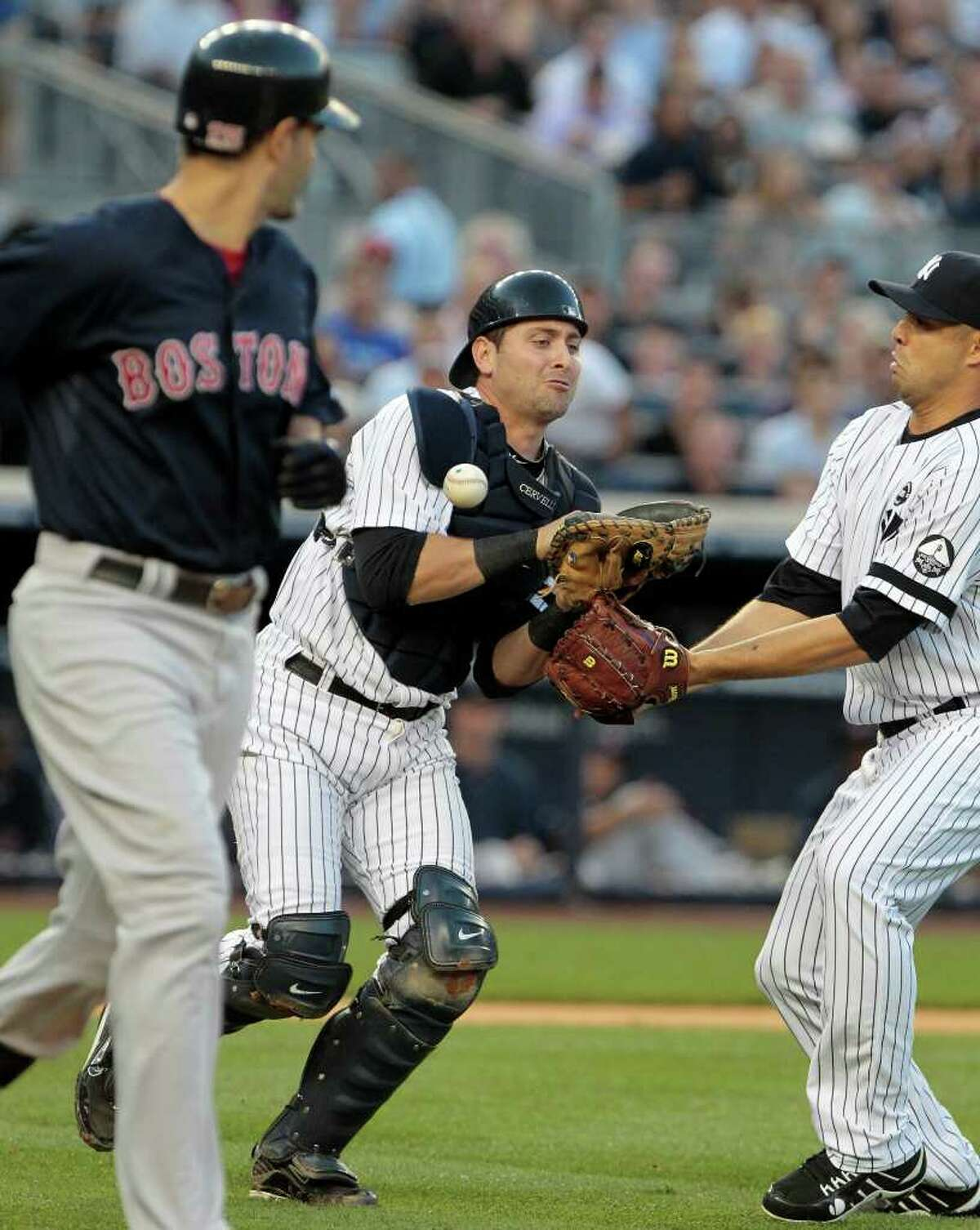 Boston Red Sox's Mike Lowell, left, and New York Yankees starting pitcher Javier Vazquez, right, watch New York Yankees catcher Francisco Cervelli, center, drop a pop fly during the second inning of a baseball game Friday, Aug. 6, 2010, in New York. (AP Photo/Frank Franklin II)