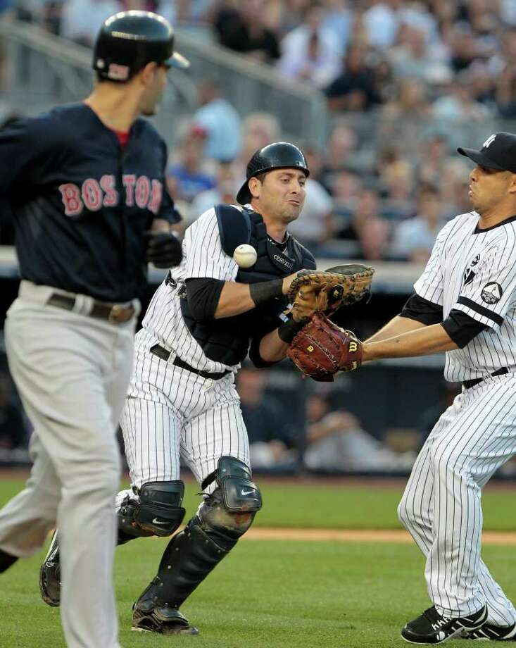 Boston Red Sox's Mike Lowell, left, and New York Yankees starting pitcher Javier Vazquez, right, watch New York Yankees catcher Francisco Cervelli, center, drop a pop fly during the second inning of a baseball game Friday, Aug. 6, 2010, in New York. (AP Photo/Frank Franklin II) Photo: AP