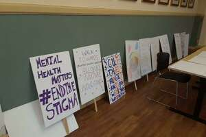 Members of Prime Time House, which provides many types of assistance to people in the Torrington area with disabilities, held their annual Walk Towards Recovery event Thursday morning, marking Mental Health Day. ABove, signs line the walls of the Torrington City Hall meeting room, where a program on World Mental Health Day was held.