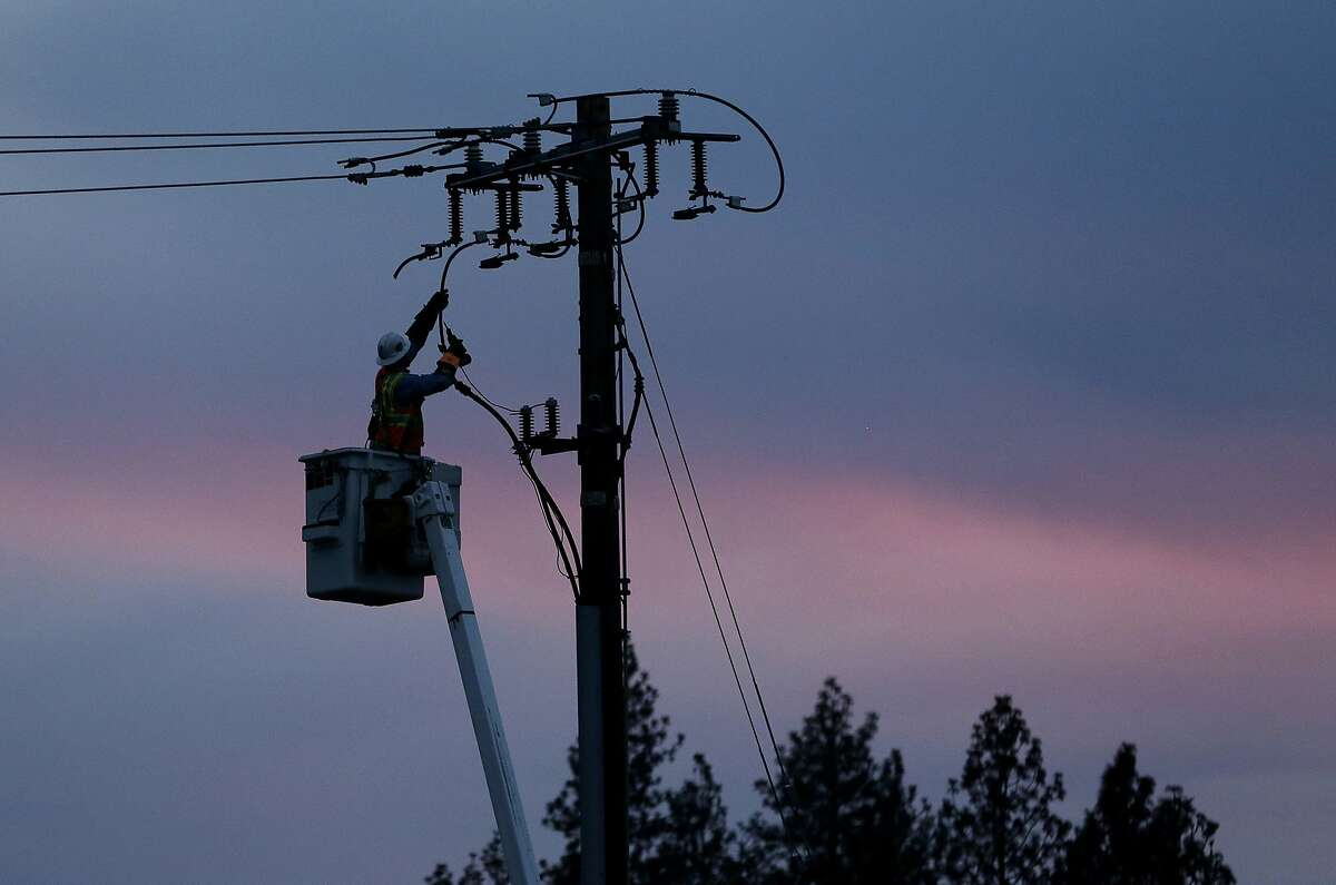 FILE - In this Nov. 26, 2018, file photo, a Pacific Gas & Electric lineman works to repair a power line in fire-ravaged Paradise, Calif. Gov. Gavin Newsom has signed, Wednesday, Oct. 2, 2019, nearly two-dozen laws aimed at preventing and fighting the devastating wildfires that have ravaged California, including a measure that addresses the precautionary power shut offs that utilities have began using more frequently to ease the risk of fires starting from electric lines. (AP Photo/Rich Pedroncelli, File)