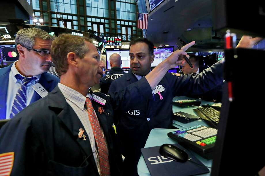 FILE - In this Oct. 7, 2019, file photo specialist Dilip Patel, right, work with traders at his post on the floor of the New York Stock Exchange. Banks led stocks broadly higher on Wall Street in afternoon trading Thursday, Oct. 10, placing the market on track to extend its gains from the day before. (AP Photo/Richard Drew, File) Photo: Richard Drew / Copyright 2019 The Associated Press. All rights reserved