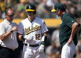 Oakland Athletics head trainer Nick Paparesta, left, and manager Bob Melvin check on Sean Murphy (12) after he was hit by a pitch during the third inning of a baseball game against the Texas Rangers, Sunday, Sept. 22, 2019, in Oakland, Calif. (AP Photo/D. Ross Cameron)