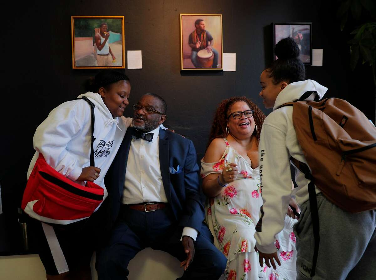 Rev. Arnold Townsend, and his daughter, Natalie Douglas, seated, greet Kayla Sherman, left, and Jasmin Corley, right, at the African American Arts & Culture Complex in San Francisco, Calif., on Monday, September 9, 2019. Townsend, a well-known leader in SF's NAACP and black church community, was devastated when his 30-something daughter died last year. But almost immediately, he received an email from Ancestry.com showing he had another daughter he knew nothing about. Douglas, a star singer, was this unknown daughter.