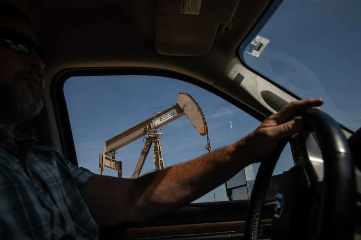 Mike Wilkinson passes a pumpjack as he drives through the oil fields near Midland. The outlook for oil prices could signal the beginning of the end for the Permian boom.