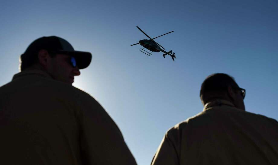 BASF TOTAL process technicians watch an Air Rescue helicopter comes in to land during an emergency response drill at the BASF TOTAL Petrochemicals plant Thursday afternoon after they got a tour of the aircraft. Photo taken on Thursday, 10/10/19. Ryan Welch/The Enterprise Photo: Ryan Welch, Beaumont Enterprise / The Enterprise / © 2019 Beaumont Enterprise