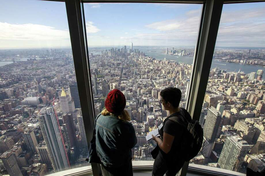 NEW YORK, NY - OCTOBER 10: Visitors look toward Lower Manhattan inside the newly renovated 102nd floor observatory of the Empire State Building on October 10, 2019 in New York City. Opening to the public on October 12, the new 102nd floor observatory is 1250 feet above street level and features 360 degree views of New York City. (Photo by Drew Angerer/Getty Images) Photo: Drew Angerer / 2019 Getty Images