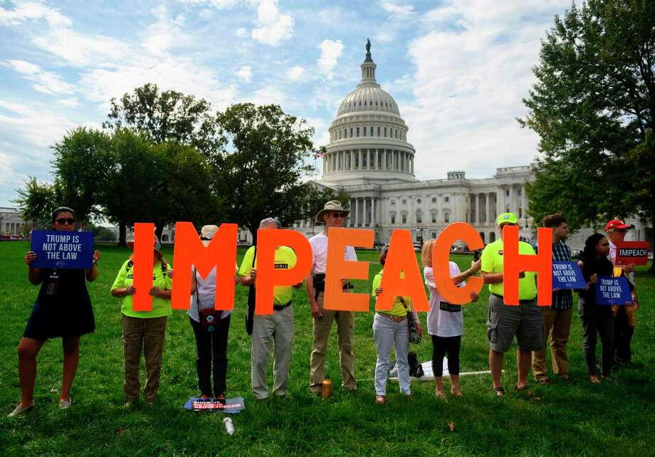 """(FILES) In this file photo taken on September 26, 2019 protesters hold up letters reading """"impeach"""" in front of the US Capitol building during the """"People's Rally for Impeachment"""" on Capitol Hill in Washington, DC. - Democratic White House hopeful Joe Biden said October 9, 2019 for the first time that Donald Trump should be impeached, arguing that the US president has """"betrayed this nation"""" and violated his oath of office. """"To preserve our Constitution, our democracy, our basic integrity, he should be impeached,"""" Biden, the former vice president whom Trump has repeatedly accused without evidence of corruption, told supporters at a rally in New Hampshire. (Photo by ANDREW CABALLERO-REYNOLDS / AFP) (Photo by ANDREW CABALLERO-REYNOLDS/AFP via Getty Images) Photo: ANDREW CABALLERO-REYNOLDS, Contributor / AFP Via Getty Images / AFP or licensors"""
