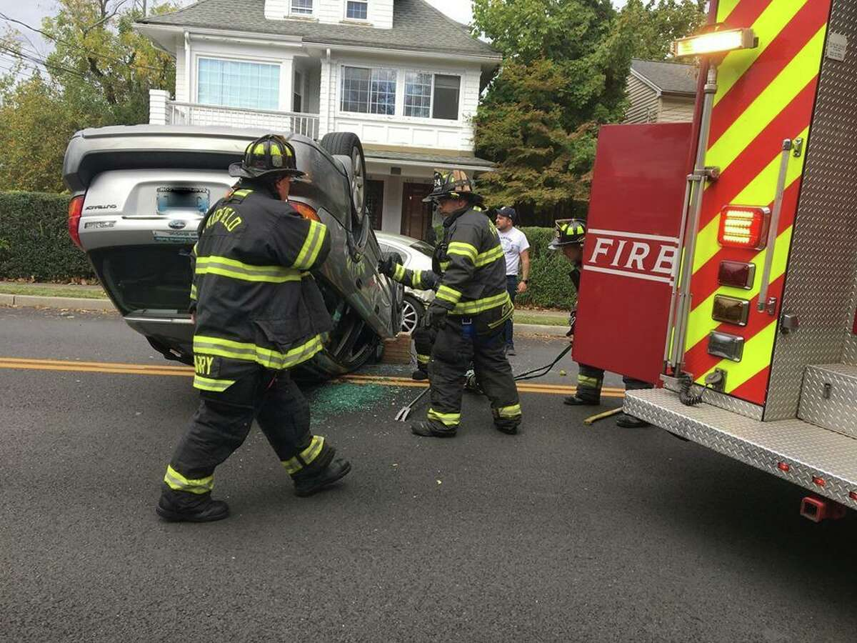 Fairfield, Conn., firefighters worked the scene of a rollover with entrapment. Photos captured by nearby resident. Any alterations made to the license plate were not made by Hearst Connecticut Media.