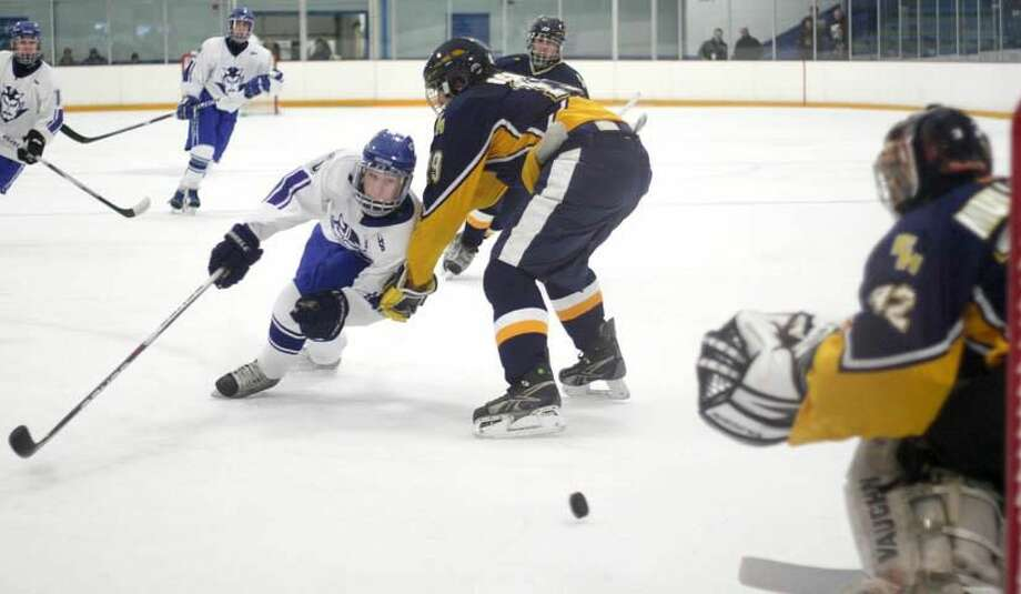West Haven's Lou Bisighini shoots around an East Haven defender in the Blue Devils' 4-0 victory last Saturday at Bennett Rink in West Haven. The Westies improved to 6-0 with the win. (Photo by Russ McCreven)