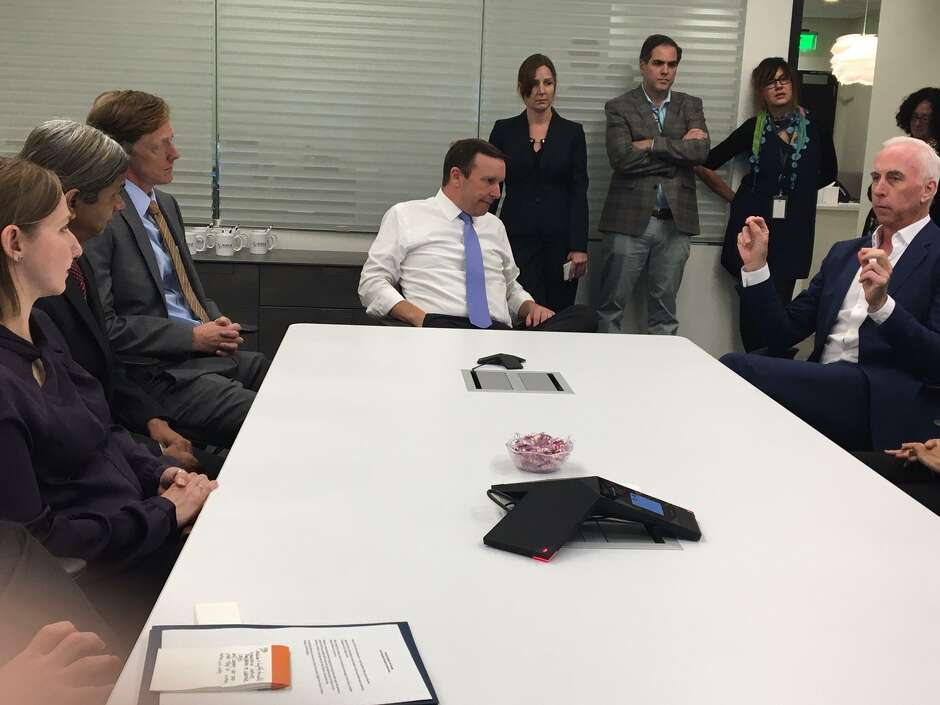 Doug Manion, CEO of Kleo Pharmaceuticals in New Haven, right, meets with city officials and others in this file photo.
