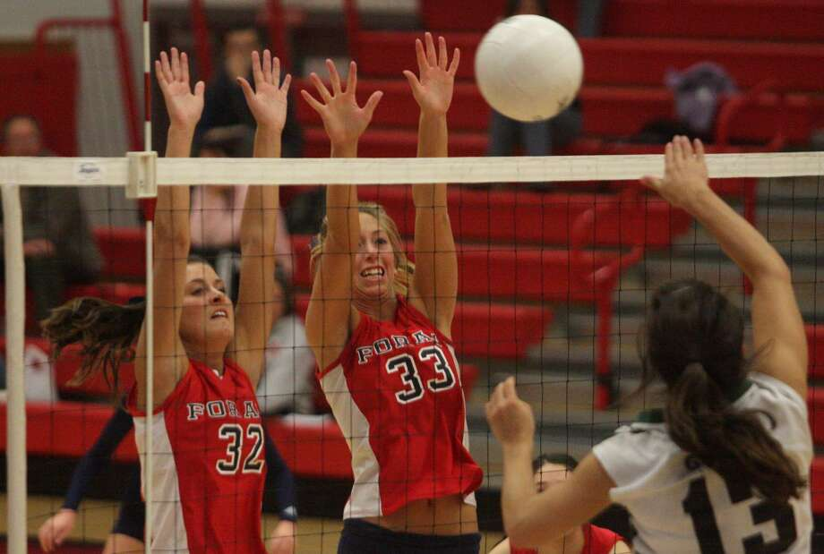 Foran's Annie Raucci (32) and Carli Matrisian block Guilford's Jenna Bellantoni in the Indians' 3-0 quarterfinal victory in the Southern Connecticut Conference tournament. (Photo by Russ McCreven).