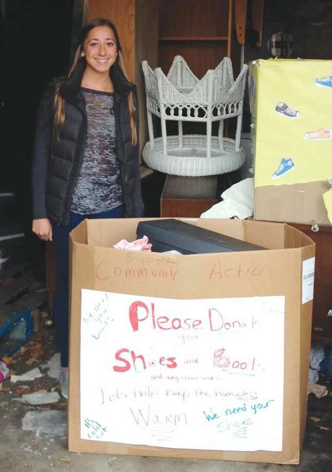 Submitted Photo Community Action Club Vice President Morgan Blume is pictured with one of two boxes of footwear the club collected for donation to Christian Community Action in New Haven.