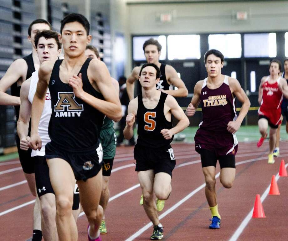 (Melanie Stengel — New Haven Register) SCC Indoor Track and Field Championships. Michael Yuan, of Amity, on his way to winning the 1000 meter race 1/30.