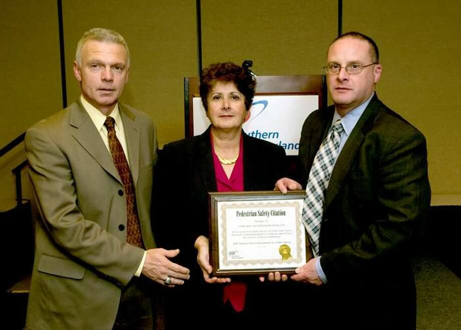Photo by Christian Abraham - Here, Orange Assistant Police Chief Edward Koether, left; and Orange Police Chief Robert Gagne, right, receive a Public Safety Award of Excellence from AAA's Public Affairs Manager Fran Mayko on behalf of the town that went 1 year without a pedestrian traffic fatality.
