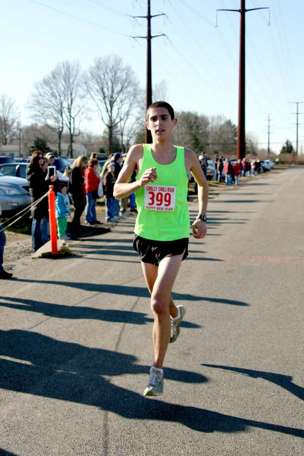 Photo by Bridget Albert - Overall Chilly Chili Run winner Matt Klein, 17, Trumbull prepares to cross the finish line. He completed the 5k in 16:05 minutes averaging a 5:11 minute mile.