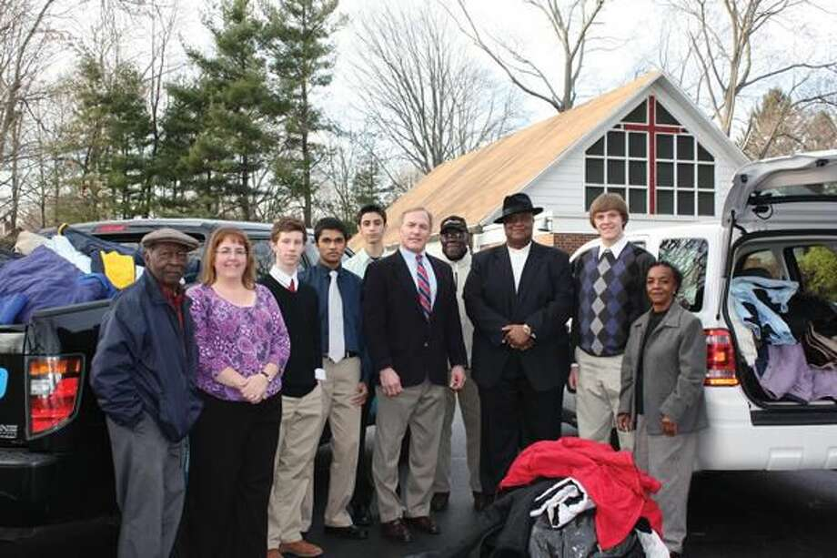 Submitted Photo Pictured left to right: Louise Goldbeck, teacher at Jonathan Law High School; students from Jonathan Law High School who helped with the coat drive; Carter Mario, President & CEO of Carter Mario Injury Lawyers; Pastor Calvin Robinson; and Laura Williams of The First Baptist Church of Milford.